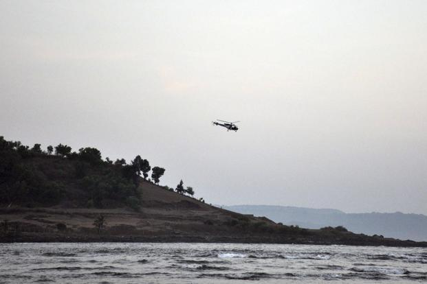 A helicopter on a search operation flies above the beach after more than a dozen college students were swept away at Murud on the Arabian Sea coast on 1 February. Photo: AP