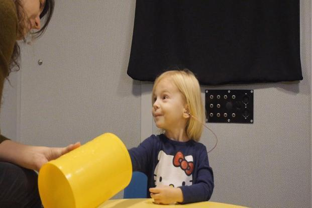 "A toddler participates in a speech perception experiment in a laboratory at the University of North Carolina at Chapel Hill, where it was conditioned to put a block in the bucket whenever she heard the ""target"" word. Photo: AP"