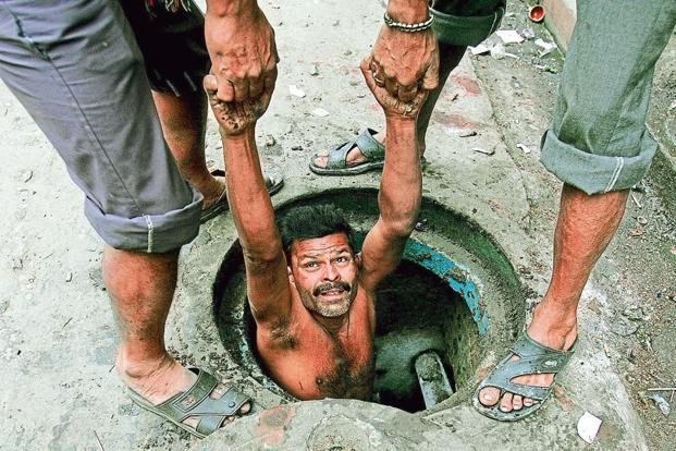 A manual labourer is lowered to clean sewage in Kolkata. Photo: Reuters