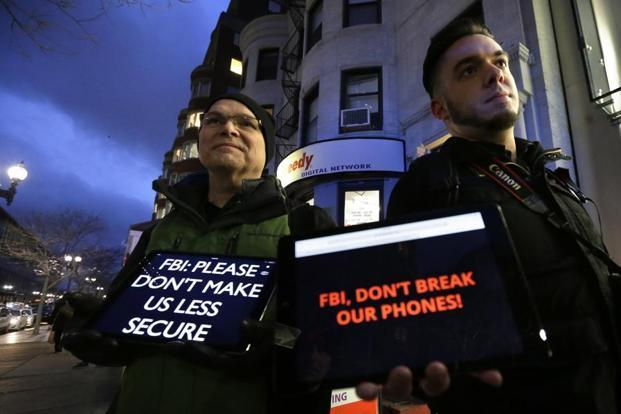 A file photo shows demonstrators displaying iPads with messages on their screens outside an Apple store in Boston. Photo: AP