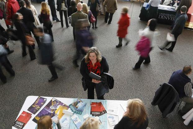 A file photo shows a job seeker talking to an exhibitor at a career fair in Denver. Photo: Reuters