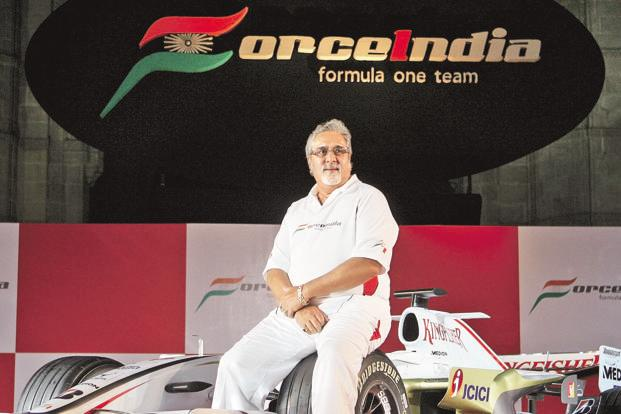 A file photo Force India co-owner Vijay Mallya posing with the team car during the unveiling function in Mumbai in February 2008. Photo: AFP