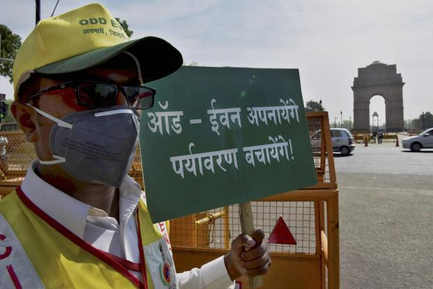 A file photo of a volunteer at a traffic signal near India Gate in New Delhi on the first day of the second phase of odd-even scheme. Photo: PTI