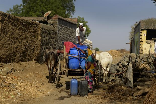 A woman collecting water in Poi Tanda, Beed, ferried on a bullock cart from a neighbouring village.