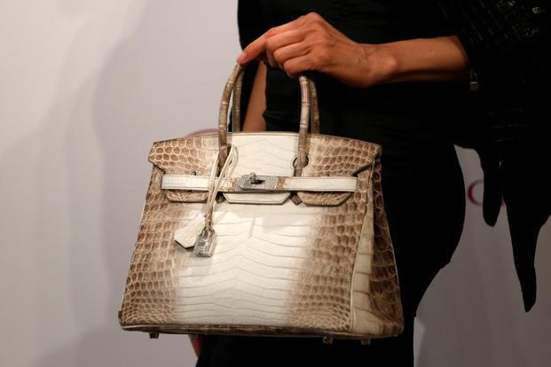 A model carries a Hermes Signature Birkin with Himalayan crocodile leather during a preview in Hong Kong. The buckle and the padlock are made of 18 carat white gold. Photo: Reuters