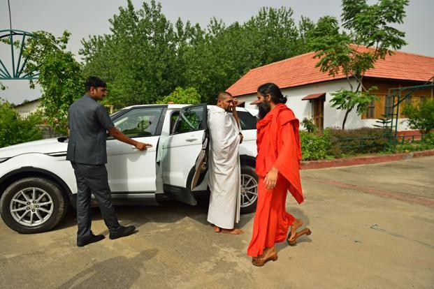 Baba Ramdev is driven around in a Range Rover Evoque.