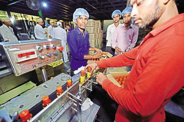 Staff at the Patanjali Ayurved hair oil packaging unit.