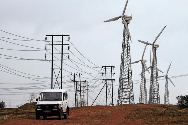 A vehicle drives past wind turbines and power transmission lines in Satara. Photo: Adeel Halim/Bloomberg