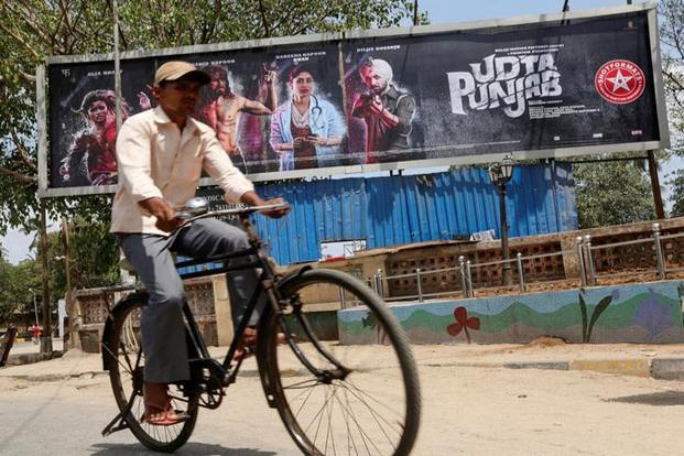 A man rides his bicycle past a poster of the movie 'Udta Punjab' in Mumbai. Photo: Reuters
