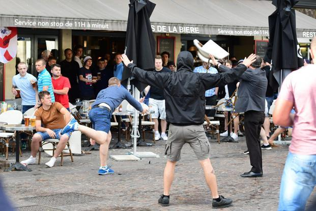 A Russian football supporter lobs a chair towards Slovakian fans sitting in a cafe in the northern city of Lille on 14 June 2016, the day before the Euro 2016 match Russia vs Slovakia at the Pierre-Mauroy stadium in the city. Photo: AFP