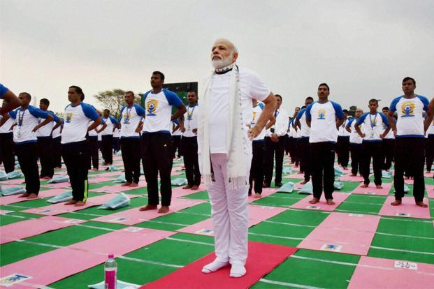 The celebrations featured a demonstration of the ancient spiritual and physical discipline by tens of thousands of people, led by PM Narendra Modi. Photo: PTI