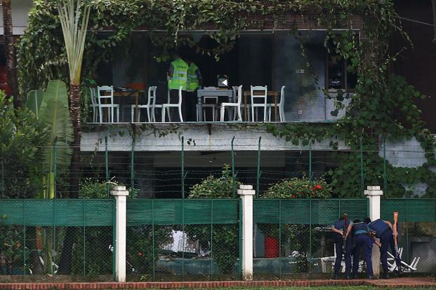 Policemen sneak a look inside the Holey Artisan Bakery and the O'Kitchen Restaurant as others inspect the site after gunmen attacked, in Dhaka, Bangladesh. Photo: Reuters