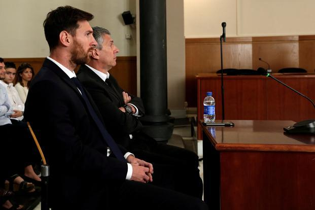 Lionel Messi (L) sits in court with his father Jorge Horacio Messi during their trial for tax fraud in Barcelona, Spain. Photo: Reuters