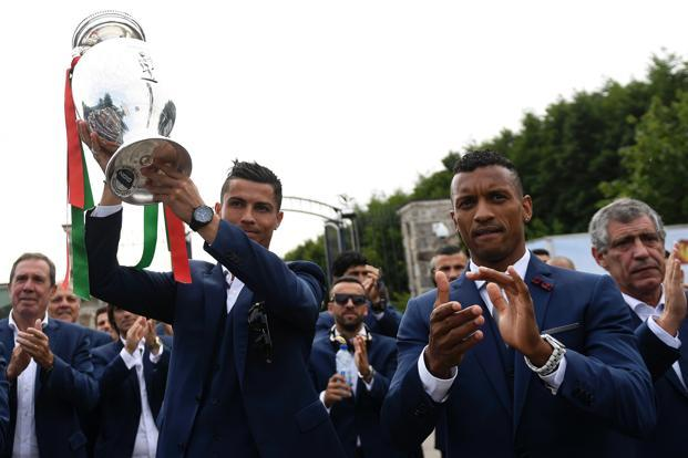 Portugal's captain Cristiano Ronaldo (left) raises the Euro 2016 football championship trophy next to Portugal's forward Nani. Photo: AFP