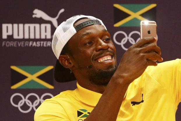 Usain Bolt uses an Apple iPhone at a press conference in Rio de Janeiro on Sunday. Photo: Reuters