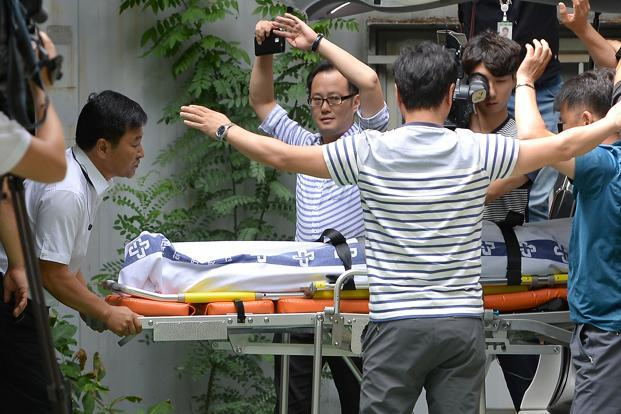 Hospital workers carry the body of Lotte Group's vice chairman Lee In-won in Yangpyeong, South Korea on Friday. Photo: AP