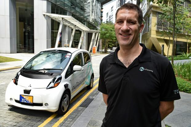 Doug Parker, COO of nuTonomy, the developer of the software stands next to a driverless taxi during an interview in Singapore. Photo: AFP