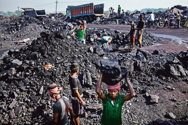 Labourers load coal into trucks at an open pit coal mine in the Bestacolla Colliery in Jharia, Jharkhand. Photo: Bloomberg