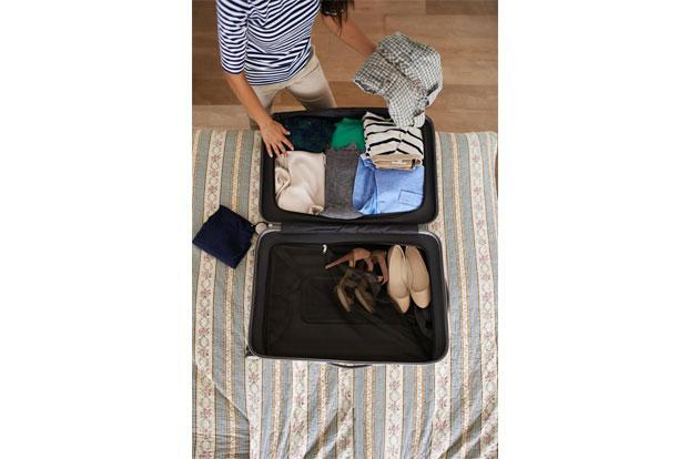 Fold suits and lay them flat on the top, and pack small things in a travel pouch. Photo: iStock.