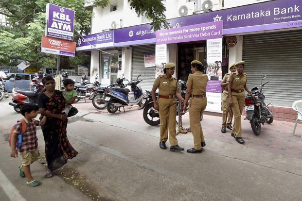 ... Police personnel guard a branch of Karnataka Bank in Chennai. Photo: PTI