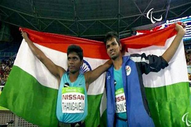 Paralympics participants Mariyappan Thangavelu (left)and Varun Singh Bhati walk with the Indian flag after winning gold and bronze medals, respectively, in the men's high jump event in Rio.