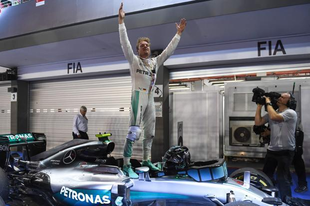 Mercedes AMG Petronas F1 Team's German driver Nico Rosberg stands on his car, as he celebrates his win at the Formula One Singapore Grand Prix in Singapore on Sunday. Photo: Mohd Rasfan/AFP