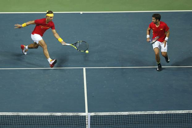 Spain's Rafael Nadal plays a shot, with compatriot Marc Lopez by his side during the Davis Cup world group play-off against India's Leander Paes and Saketh Myneni in New Delhi, India on Saturday. Photo: AP