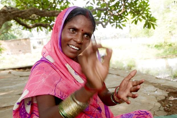 Seema Mahila Kisan, an elected ward member and farmer from the Mahadalit community demonstrates how she has learnt to sign on documents.