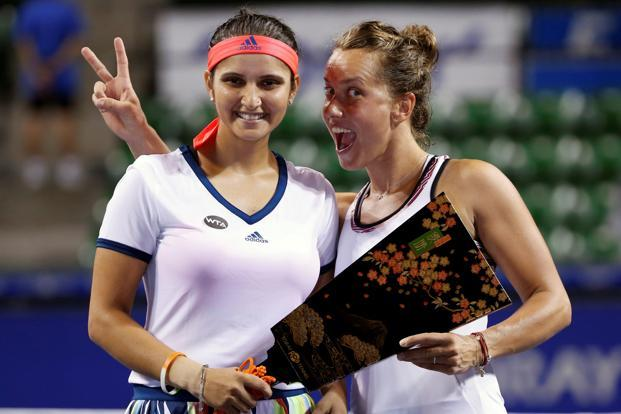 Sania Mirza (left) and Barbora Strycova of Czech Republic pose with their victory trophy. Photo: Reuters