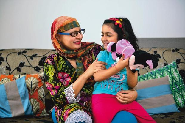 Deepika Jauhari, a breast cancer survivor, with her daughter at her house in Noida, near Delhi. Photo: Pradeep Gaur/Mint