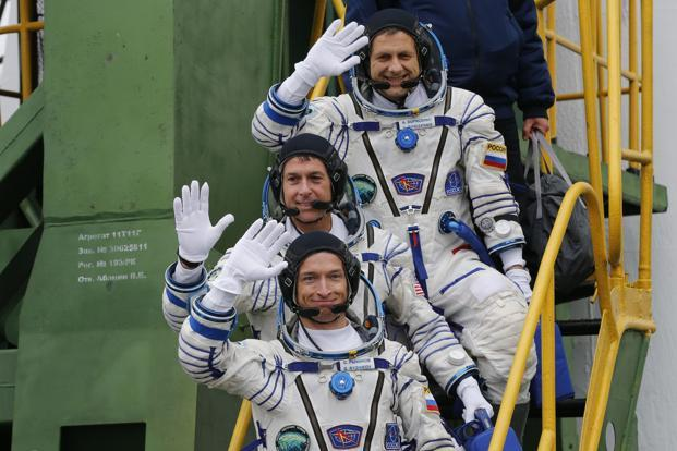 Russian cosmonauts Sergey Ryzhikov (bottom) and Andrey Borisenko (top) and US astronaut Shane Kimbrough wave as they board the Soyuz MS-02 spacecraft at Baikonur cosmodrome on 19 October 2016. Photo: AFP
