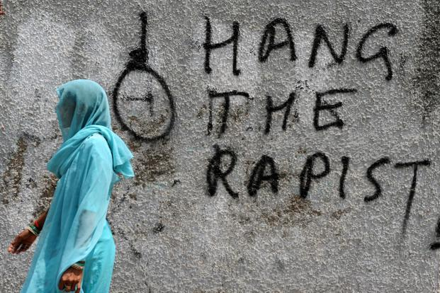 A woman walks past graffiti against rape written on a wall in New Delhi on in April 2013. Photo: AFP