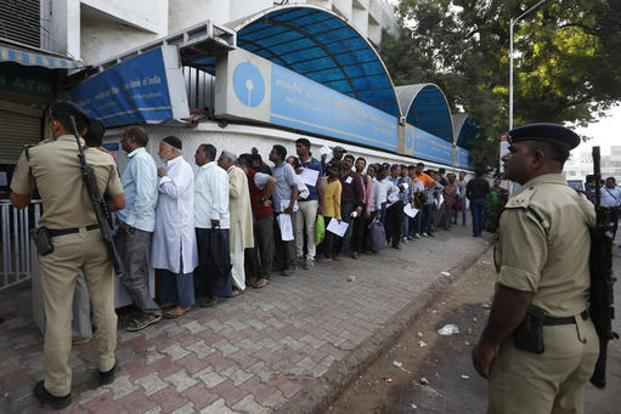 Policemen stand guard as people queue up outside a bank to exchange and deposit Rs500 and Rs1,000 denominations on Thursday. Photo: AP