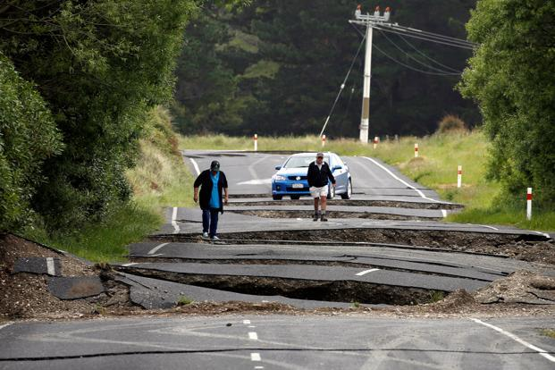 Local residents look at damage caused by an earthquake along state highway one near the town of Ward, south of Blenheim on New Zealand's South Island on 14 November. Photo: Reuters