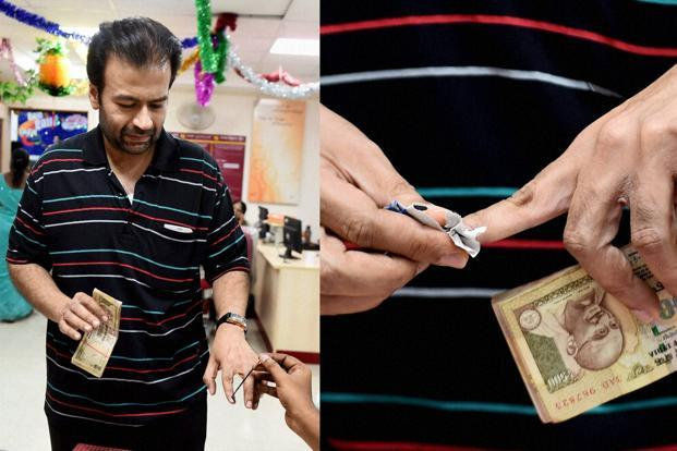 A customer tries to remove the indelible ink which was applied on his finger before exchanging old currency notes at a Punjab National Bank branch in Chennai on Wednesday. Photo: PTI