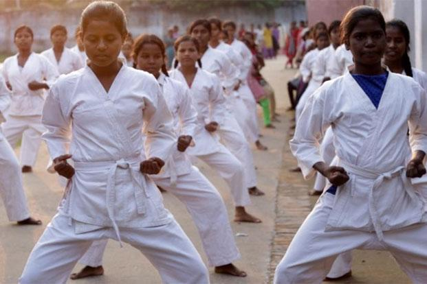 Prerana Hostel's adolescent girls in their karate uniforms, practising with impeccable coordination