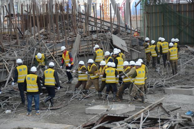 Rescue workers search at the site where a power plant's cooling tower under construction collapsed in Fengcheng China on Thursday. Photo: Reuters