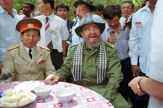Castro (centre) wearing a Viet Cong hat and checkered scarf, samples root fibers, the staple food of Vietnamese living in the underground tunnel network during the Vietnam War, in Vietnam in this 11 December 1995 picture. AP