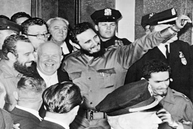 Castro (center) holding a cigar, stands with Soviet Premier Nikita Khrushchev, (center left), outside Hotel Theresa in Harlem, New York on 20 September 1960. Castro was in the US during his first visit to the United Nations after coming to power. AP