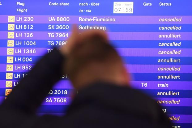 A flight passenger stands in front of a board displaying cancelled flights of German airline Lufthansa in Frankfurt. Photo: AFP