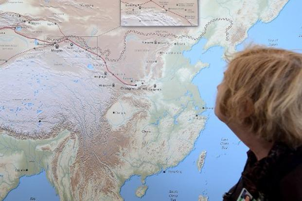 A woman walks past a map of China and Central Asia with red line signifying the ancient trade route known as the Silk Road. Photo: AFP