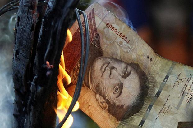 A man burns a 100-bolivar bill during a protest in El Pinal, Venezuela on Friday. Photo: Reuters