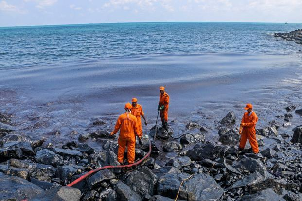 Members of the Pollution Response Team removing black oil washed ashore as a thick oily tide from the sea lapped at the coast, a day after an oil tanker and an LPG tanker collided near Kamarajar Port in Ennore on Monday. Photo: PTI