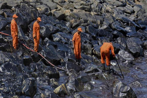 Indian Coast Guard personnel work to clear the slick after an oil spill polluted the Ennore beach on the Bay of Bengal coast near Chennai. Photo: AP