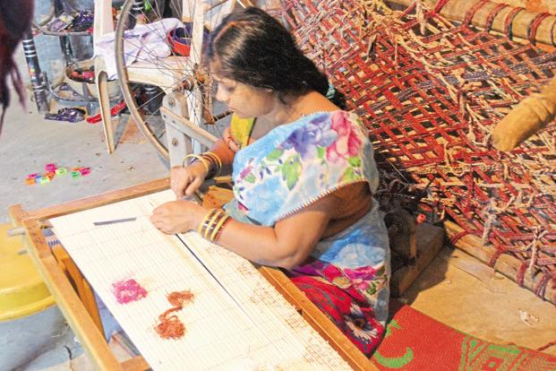 A woman works on a tie-and-dye frame in a handloom cluster in Odisha. Photo: Vimages.In