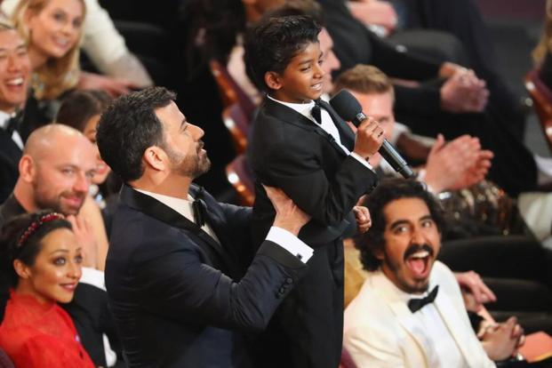 Dev Patel who was nominated for Best Supporting Actor for his role in 'Lion' watches host Jimmy Kimmel lift Sunny Pawar (centre) at the Oscars.