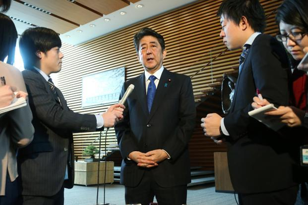 "Japan's Prime Minister Shinzo Abe (centre) speaks to journalists in Tokyo on Monday. He  called the firing of four missiles by North Korea a ""new stage of threat"" emanating from the neighbouring country. Photo: AFP"