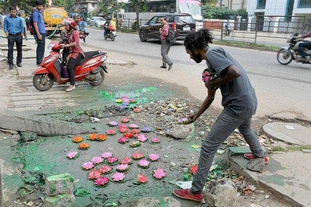 Another of Nanjundaswamy quirky installation. He transforms this pothole in Bengaluru into a lagoon full of lotus flowers. Shailendra Bhojak/PTI