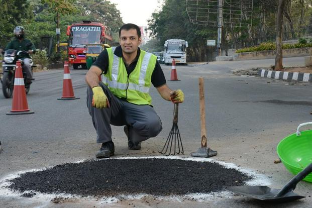 Prathaap uses a flat handheld tool to smoothen the surface and compact the asphalt to fill up a pothole in Benguluru. WhatsApp Prathaap at +91-814 POTHOLE and he'll repair the pothole for you for a fee. Hemant Mishra/Mint