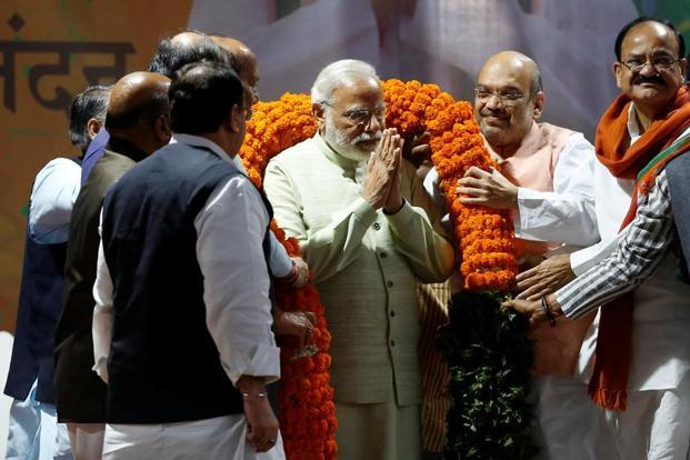 Narendra Modi (centre) is being garlanded by party leaders at BJP headquarters in New Delhi.
